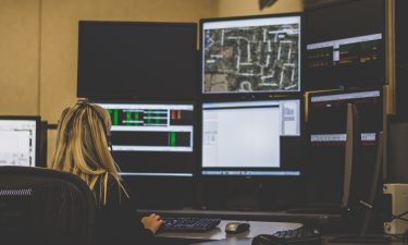 image of female dispatcher at her station - links to the monthly 911 call totals page